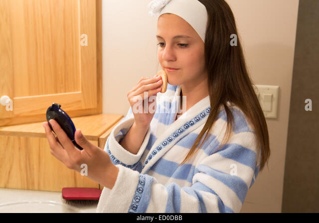 Girl standing in bathroom applying foundation powder - Stock Image