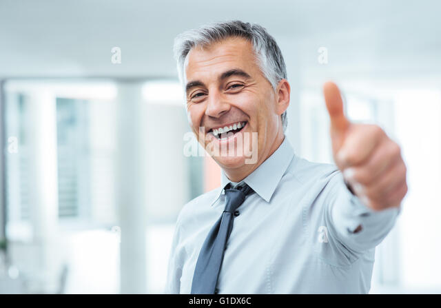 Cheerful businessman thumbs up posing and smiling at camera - Stock Image