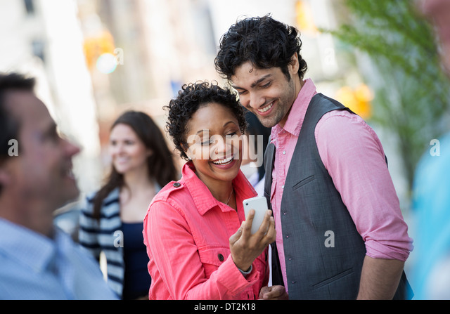 People outdoors in spring time New York City park Four people men and women A couple looking at a mobile phone screen - Stock Image