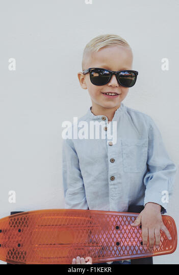 Little boy in trendy over sized sunglasses borrowed from a parent standing clutching a skateboard looking at the - Stock Image