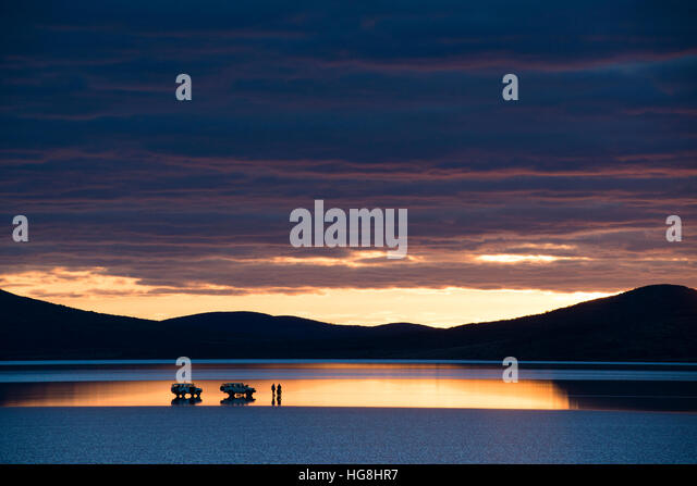2 cars and some people stopped on a reflective lake during sunset with mountains - Stock Image