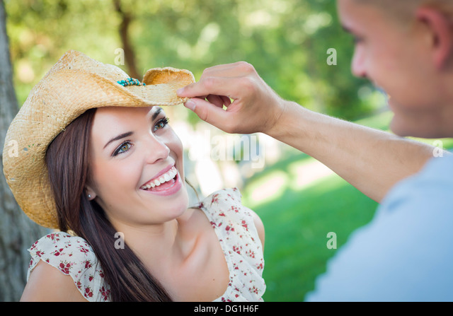 Happy Mixed Race Romantic Couple with Cowboy Hat Flirting in the Park. - Stock-Bilder