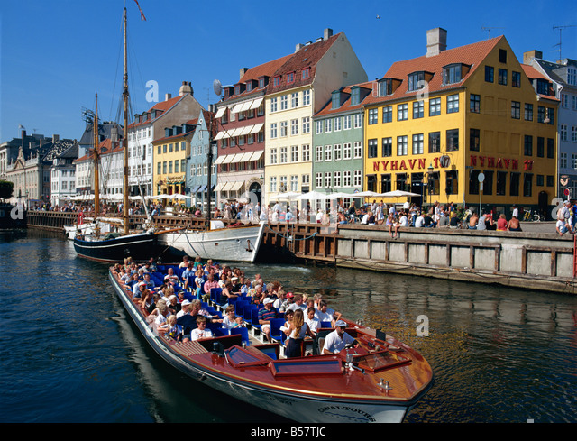 Tourists on boat trip pass painted buildings on the busy waterfront of Nyhavn, Copenhagen, Denmark, Scandinavia, - Stock Image