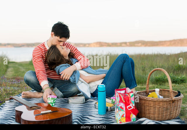 Man kissing girlfriend during picnic - Stock Image