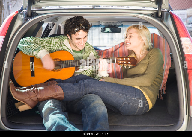 Couple sitting in back of car with guitar - Stock-Bilder