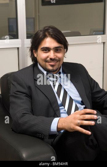 Smiling businessman sat inside office smiling Beirut Lebanon Middle East - Stock Image