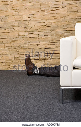 Man tied up behind sofa - Stock Image
