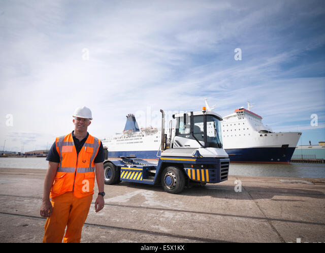 Portrait of shipping container truck driver and ship in port - Stock Image
