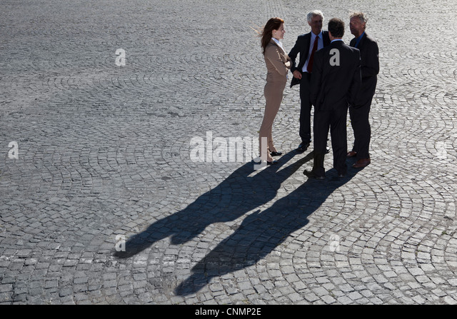 Business people talking on cobbled road - Stock Image