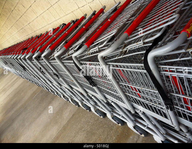A long line of shopping carts create an interesting perspective - Stock Image