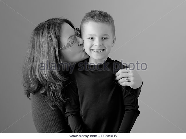 Mother kissing son on cheek. - Stock Image