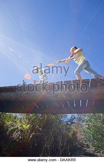 Girl chasing boy with fishing net on footbridge - Stock Image