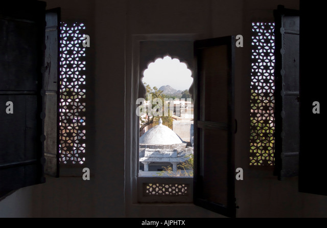 View of Ghanerao village through lattice sreened windows at Ghanerao Royal Castle heritage hotel, Rajasthan, India - Stock Image