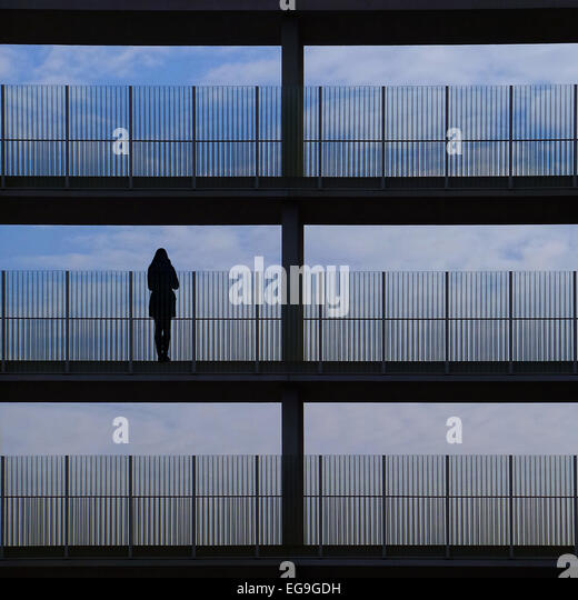 Silhouette of woman standing on balcony - Stock Image