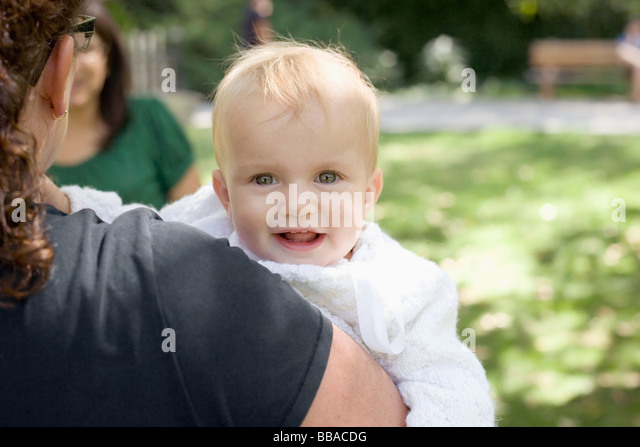 A mother carrying her baby girl, over the shoulder view - Stock-Bilder
