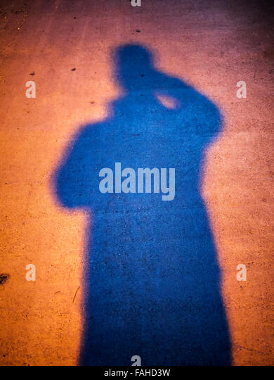 Shadow of a person on the street at night - Stock Image