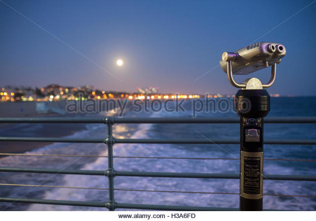 A full moon rising over the beach at Santa Monica pier with heavy surf. - Stock Image
