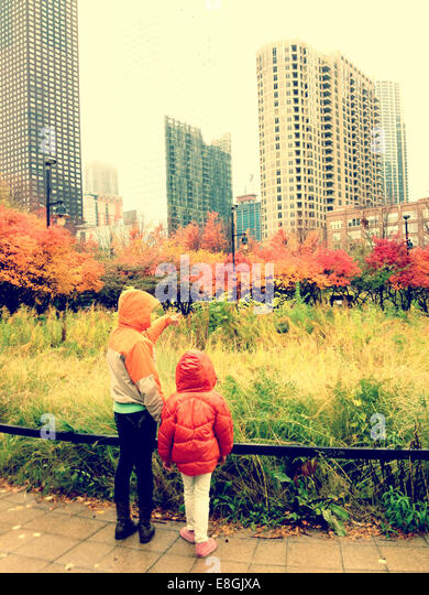 Rear view of two sisters standing in park, Chicago, Illinois, America, USA - Stock Image