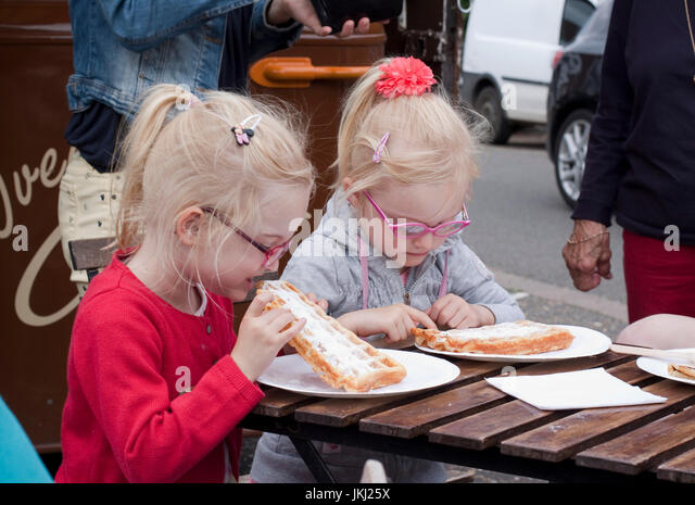Two young blonde sisters/twins eating waffles at an outdoor cafe - Stock Image