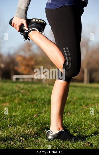 Mid adult woman performing warm-up exercises in park, low section - Stock Image