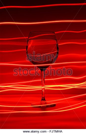 Close-Up Of Wine Glass Against Red Abstract - Stock-Bilder