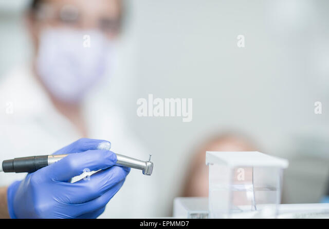 Dentist holding amalgam carrier - Stock Image
