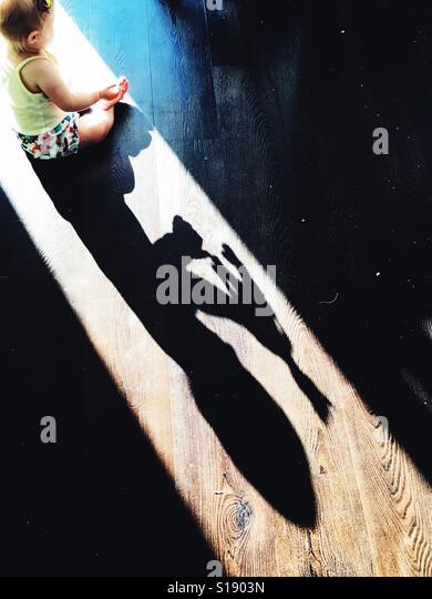 Shadow of girl playing with giraffe - Stock-Bilder