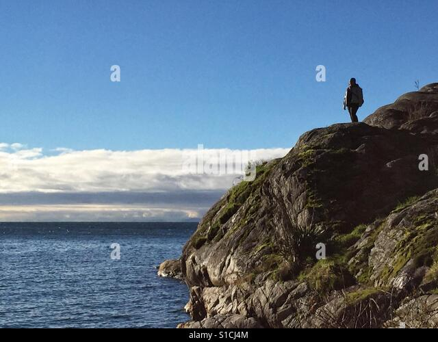 Solitary person at the edge on a cliff next to the sea, looking at the marine landscape. - Stock-Bilder