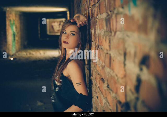 Portrait Of Beautiful Young Fashion Model Standing Against Brick Wall - Stock Image