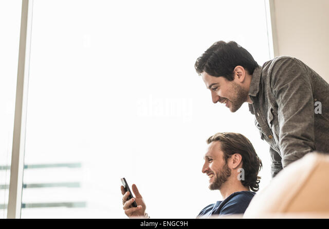 Two business men looking at a smart phone and smiling. - Stock Image