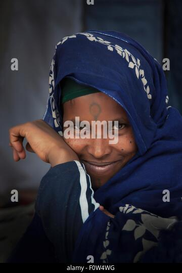 Portrait of smiling Amhara woman wearing blue traditional clothing, Ethiopia, Africa - Stock Image