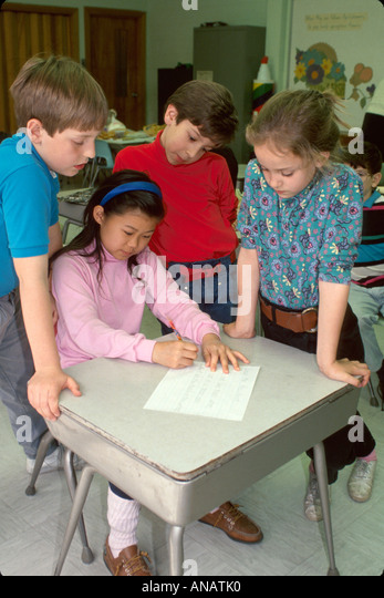 New Jersey Westwood class students Asian girl writing desk assignment writing letter to elected representative - Stock Image