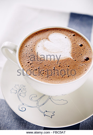 Cup of hot chocolate with whipped cream shaped heart - Stock Image