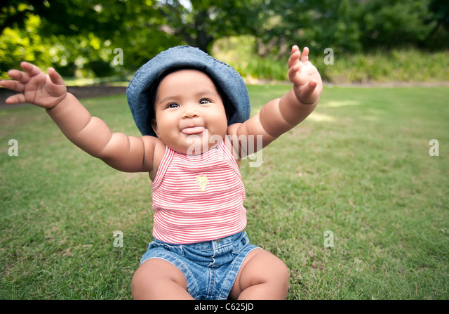 baby with arms in the air and blowing raspberries - Stock Image