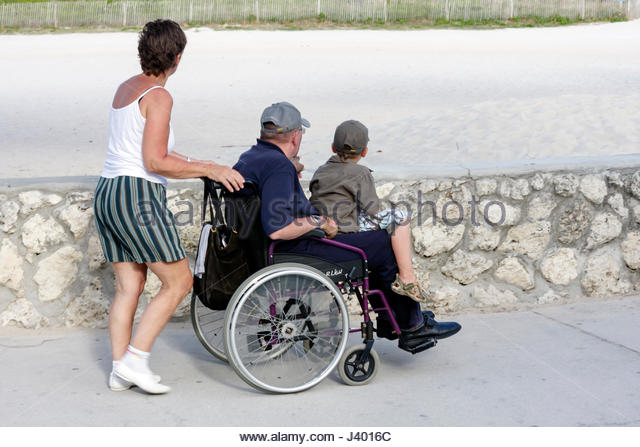 Miami Beach Florida Lummus Park walkway coral rock wall woman man boy family wheelchair push disabled - Stock Image