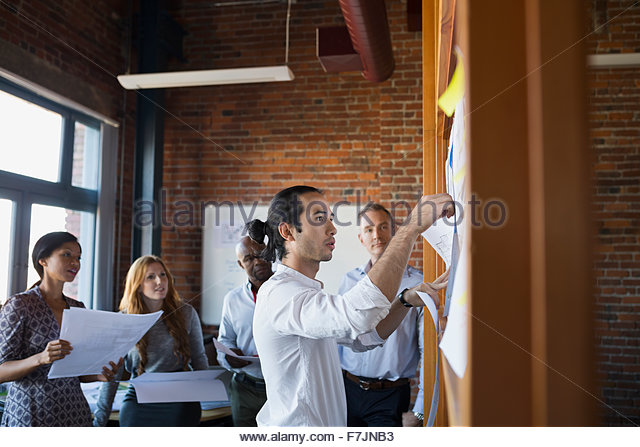 Business people reviewing paperwork in meeting - Stock Image