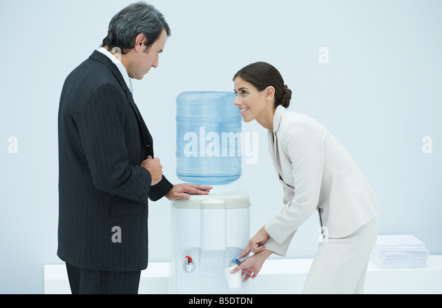 Two professionals chatting beside water cooler, woman filling disposable cup - Stock-Bilder