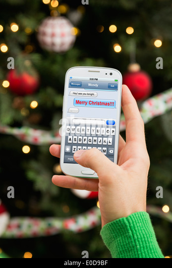 Man's hand sending Christmas wishes by cell phone - Stock-Bilder