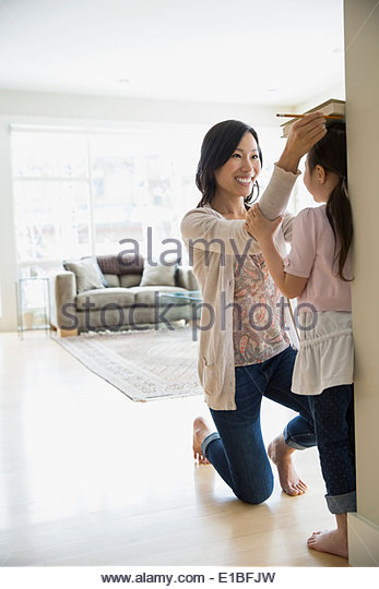 Mother measuring daughters height in living room - Stock Image