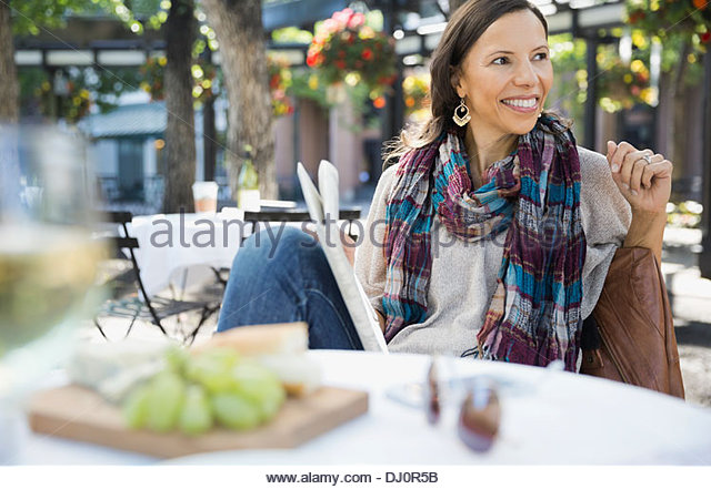 Beautiful woman with newspaper at outdoor cafe - Stock Image