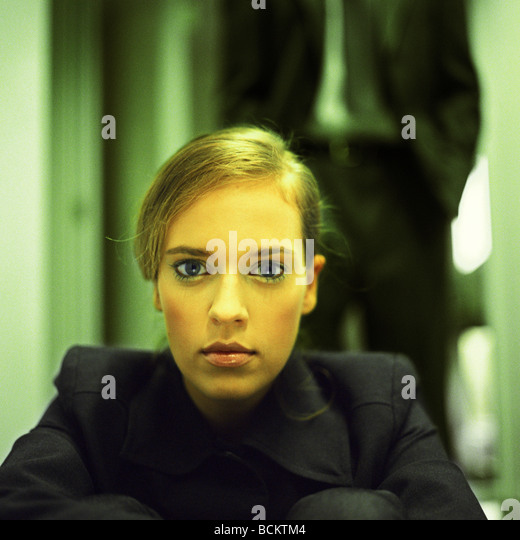 Woman looking at camera, man standing in background - Stock Image