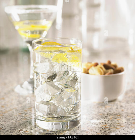 Glass of gin and tonic on a bar counter with empty cocktail glasses and cashew nuts out of focus behind. - Stock Image