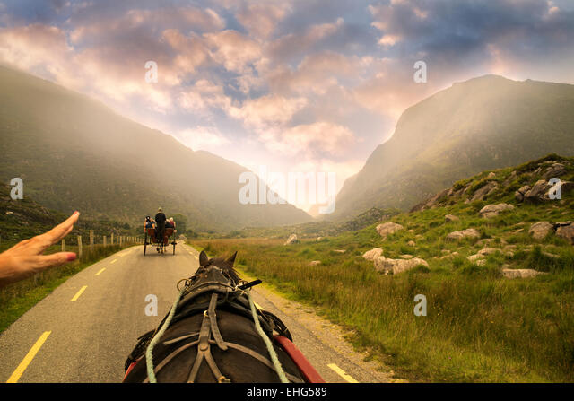 Horse drawn Jaunting Car on road with hand pointing the way. Gap of Dunloe, Ireland - Stock Image