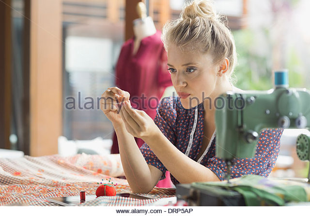 Fashion design threading needle in studio - Stock Image