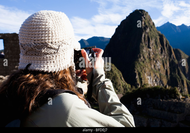 A teenager takes a photo of Machu Picchu, the ancient ruins in the Sacred valley of Peru. - Stock Image