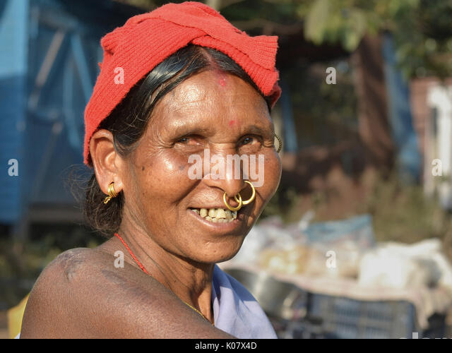 Elderly Indian Adivasi market woman with two golden nose rings and distinctive tribal earrings. - Stock Image