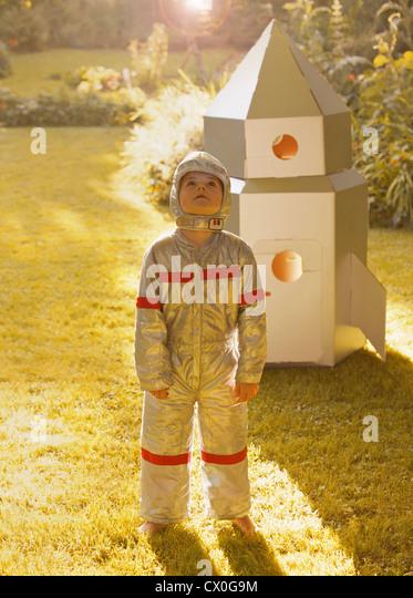 Boy Wearing Space Suit Standing in front of Cardboard Rocket Spacecraft - Stock Image