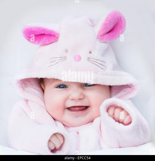 Laughing happy baby girl sitting in a white stroller in a bunny dress-up - Stock Image