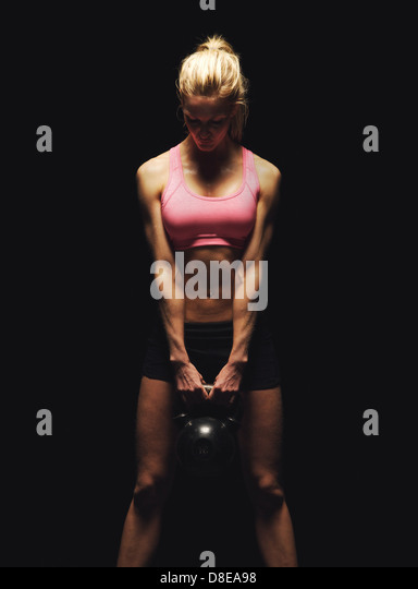 Fitness woman doing a weight training by lifting a heavy kettlebell - Stock Image