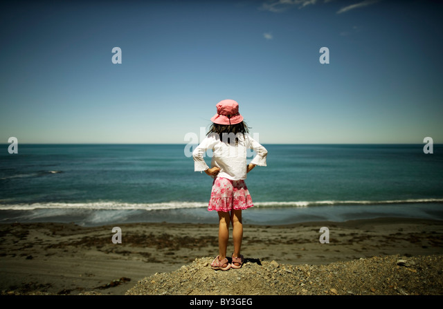 Girl looks at ocean, Wellington, New Zealand - Stock Image